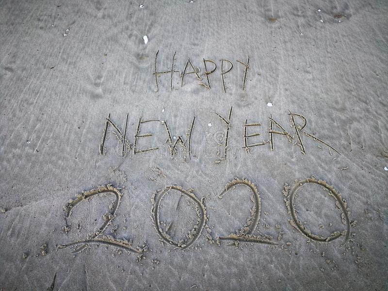 Happy new year 2020, lettering on the beach with wave and clear blue sea. Numbers 2020 year on the sea shore. stock photo
