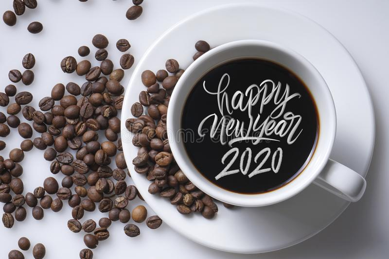 Happy new year 2020. White cup of black coffee and happy new year 2020 great hand latter on white with robusta coffee beans stock image